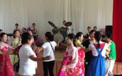 見学者と踊る北朝鮮の女子中学生