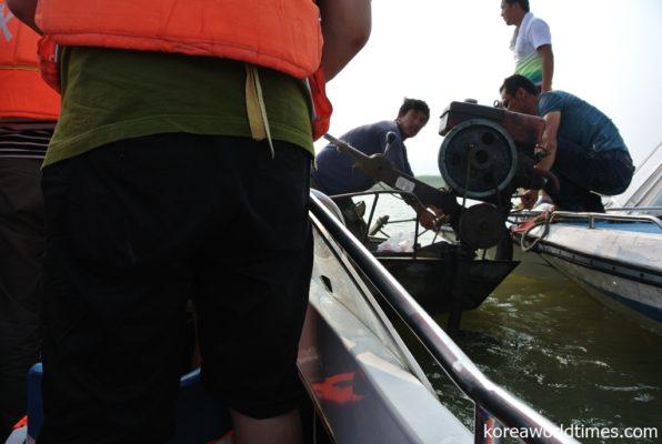 漁民風商人が100元の北朝鮮グッズを水上で売る