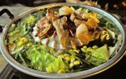 鉄板の山で肉を焼き、周囲のスープで野菜を煮込むムーガタ